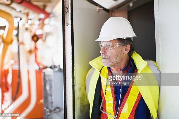 Worker standing in doorway on oil rig