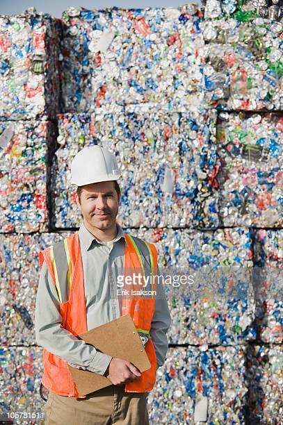 worker standing in front of crushed aluminum cans - aluhut stock-fotos und bilder