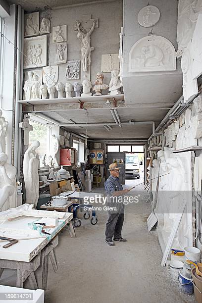 Worker standing in relief carving shop