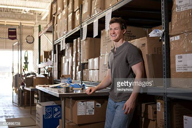 worker standing in warehouse, leaning against shelving - heshphoto stock pictures, royalty-free photos & images