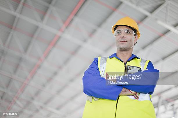 worker standing in warehouse - protective workwear stock pictures, royalty-free photos & images