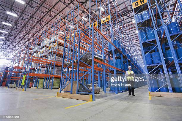 worker standing in warehouse - drum container stock photos and pictures