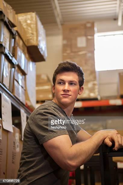 worker standing in warehouse - heshphoto stock-fotos und bilder