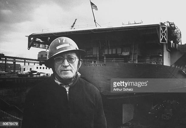 Worker standing near USS Lexington at the Brooklyn Navy Yard which Defense Dept has ordered closed