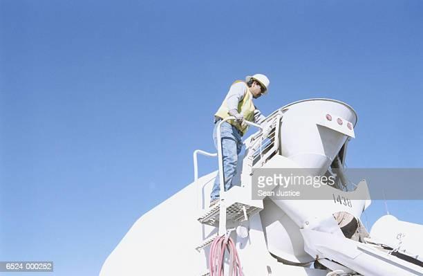 Worker Standing on Dump Truck