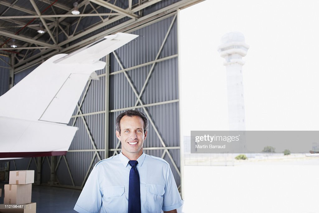 Worker standing with airplane in hangar : Stock Photo