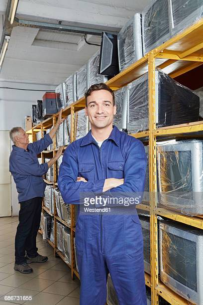 Worker standing with arms crossed in monitor storage of computer recycling plant