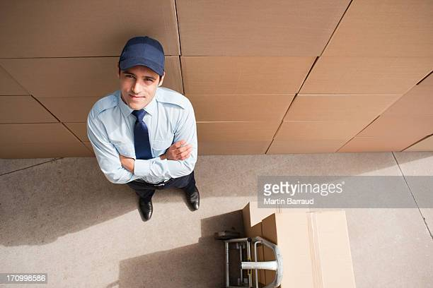 worker standing with boxes and hand truck - dolly martin stock photos and pictures