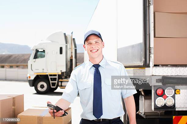 Worker standing with boxes near semi-truck