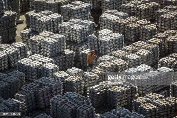 A worker stands among bundles of aluminum ingots sitting stacked at a China National Materials Storage and Transportation Corp stockyard in Wuxi...