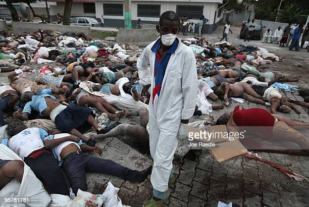 A worker stands among the bodies of some of the thousands of people killed by a massive earthquake that lay piled outside the morgue January 14 2010...