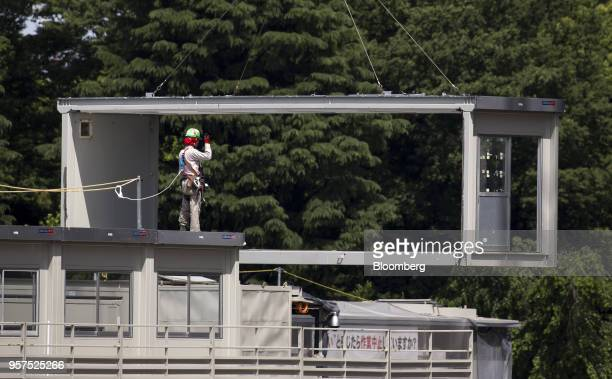 A worker stands as a temporary housing unit is being carried at the construction site of the New National Stadium a venue for 2020 Summer Olympics...