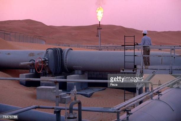 A worker stands at a pipeline watching a flare stack at the Saudi Aramco oil field complex facilities at Shaybah in the Rub' al Khali desert on March...