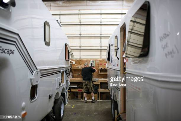 Worker stands at a workbench in between two trailers on the assembly floor at Escape Trailer Industries in Chilliwack, British Columbia, Canada, on...