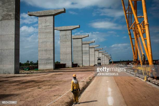 A worker stands at the Catembe side of the construction site of the MaputoCatembe Bridge which will be the longest suspension bridge in Africa once...