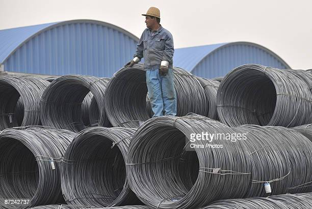 A worker stands atop a roll of steel at a steel product market on May 15 2009 in Shenyang of Liaoning Province China According to the National...