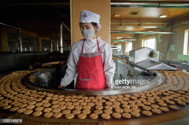 """Worker stands before a machine on a production line for """"Taeha"""" brand cakes at the Unha Taesong Foodstuff Factory in Pyongyang on April 6, 2021."""