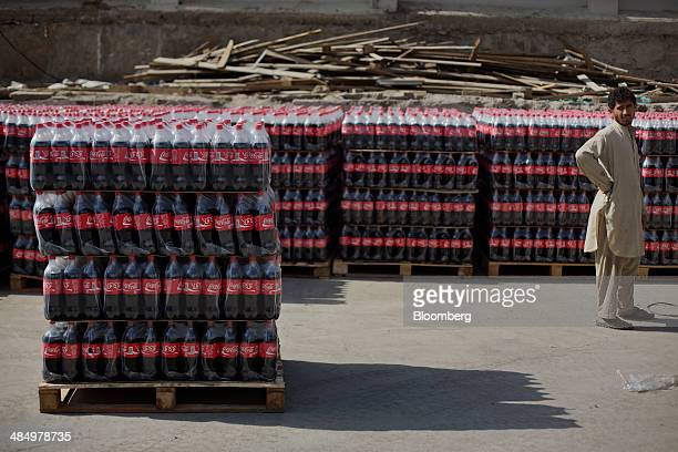 A worker stands before loading pallets of CocaCola Co beverage at the Habib Gulzar NonAlcoholic Beverage Ltd bottling facility in Kabul Afghanistan...
