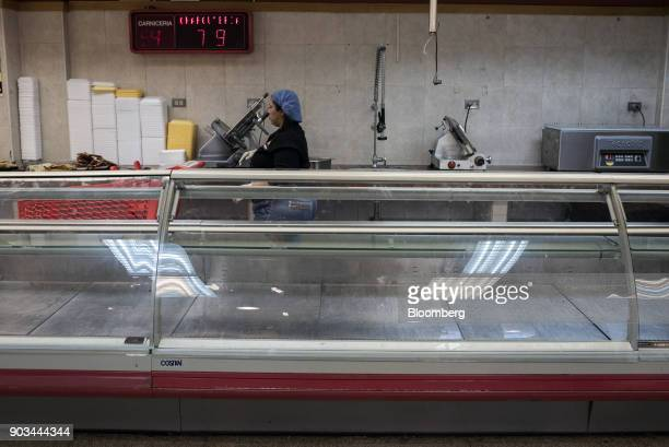 A worker stands behind an empty meat counter at a grocery store in Caracas Venezuela on Tuesday Jan 9 2018 Hordes of desperate shoppers emptied...