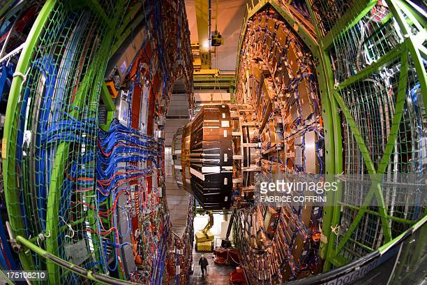 A worker stands below the Compact Muon Solenoid a generalpurpose detector at the European Organisation for Nuclear Research Large Hadron Collider...