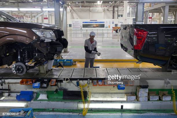 A worker stands between Nissan Motor Co Navara pickup trucks on an assembly line at the company's plant in Samut Prakan Thailand on Tuesday April 25...