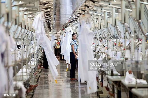 A worker stands between rows of sewing machines in the garment area at a PT Sri Rejeki Isman factory in Sukoharjo Java Indonesia on Wednesday March...