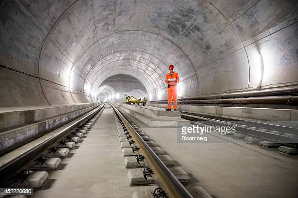 A worker stands between train tracks in this arranged photograph taken inside the east section of the Gotthard Base Tunnel in Faido Switzerland on...