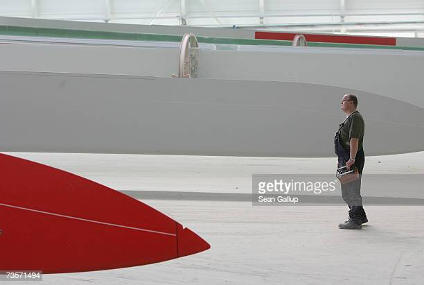 A worker stands by 45 meter long wind turbine blades at the Nordex wind turbine factory March 12 2007 in Roctock Germany Nordex has seen its sales...