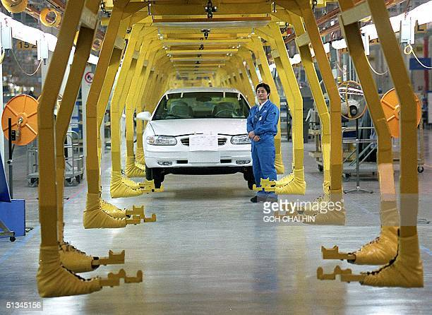 A worker stands by an assembly line making Buick sedans at the new 152 billiondollar US auto giant General Motors plant in Shanghai's Pudong...