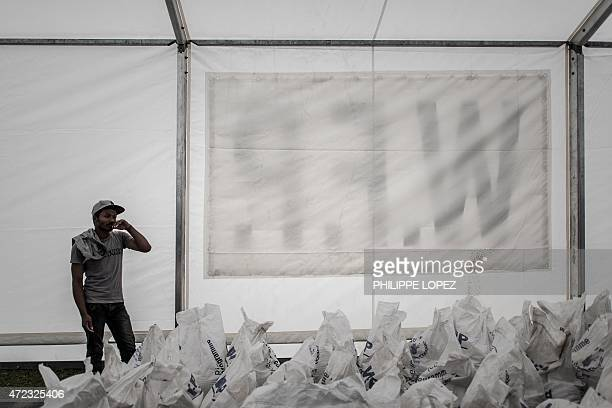 A worker stands by bags of rice stored under a tent of the World Food Programme in Deurali village of Nepal's Gorkha district on May 6 2015 The...