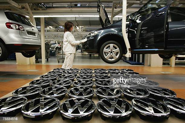 A worker stands by Volkswagen hood ornaments at the Golf production line at the Volkswagen factory February 15 2007 in Wolfsburg Germany Volkswagen's...