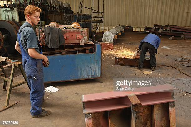 A worker stands by while a welder welds a part of a ship at the Blohm Voss shipyard August 13 2007 in Hamburg Germany Northern Germany with its busy...