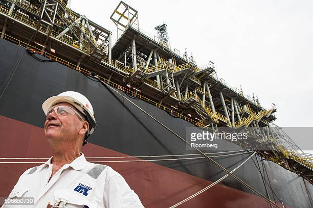 A worker stands dockside next to the Tullow Oil Plc Prof John Evans Atta Mills Floating Production Storage and Offloading vessel at the Sembcorp...