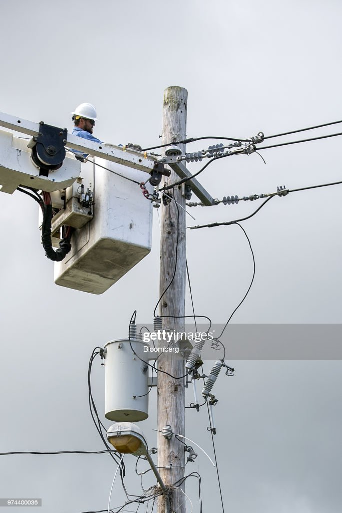 A worker stands in a cherry picker while fixing power lines on a utility pole in the town of Limones, Yabucoa, Puerto Rico, on Friday, May 18, 2018. The bankrupt U.S. commonwealth's investment bankers last week started sounding out suitors for the eight-decade-old monopoly known asPrepa, whose rickety infrastructure was almost erased by Hurricane Maria in 2017. The halting efforts to repair the damage and improve the antiquated grid have been the central obstacle in recovery. Photographer: Xavier Garcia/Bloomberg via Getty Images