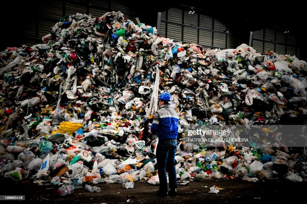A worker stands in front a pile of garbage for recycling at Valorsul, a waste treatment plant, in Lisbon on January 22, 2013.
