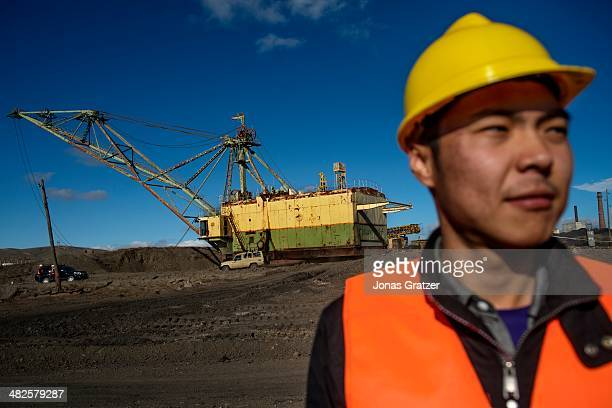 Worker stands in front of a crane that was onced owned by the Soviet Union who dug for coal in Mongolia. Mongolia today is known for its large...