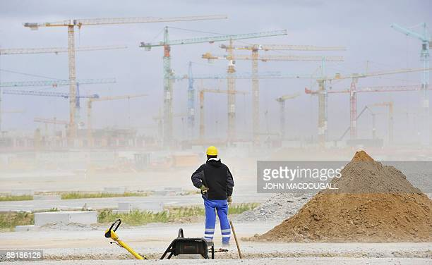 A worker stands in front of the construction site for the main terminal of Berlin's new Airport the BerlinBrandenburg International Airport June 3...