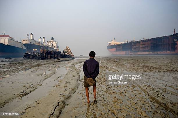 Worker stands in the muddy water in front of mega freighters that have been parked on Chittagong beach to be disassembled. Where do the mega...