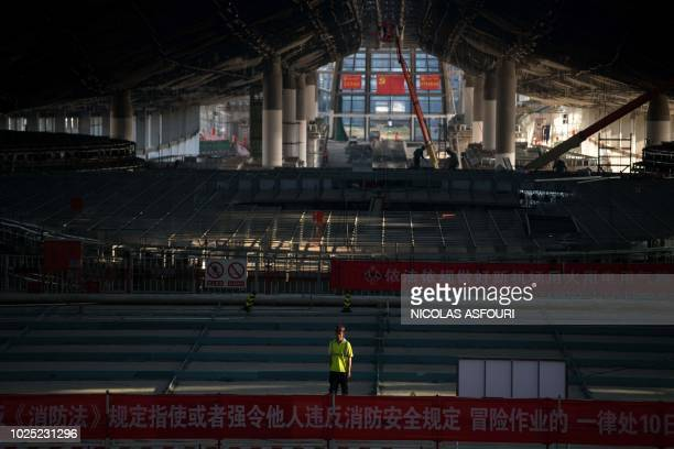 A worker stands inside the new roofed terminal building of the BeijingDaxing New Airport in Beijing on August 30 2018 The building which is set for...