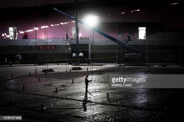 A worker stands inside the underconstruction National Speed Skating Oval the venue for speed skating events at the Beijing 2022 Winter Olympics in...