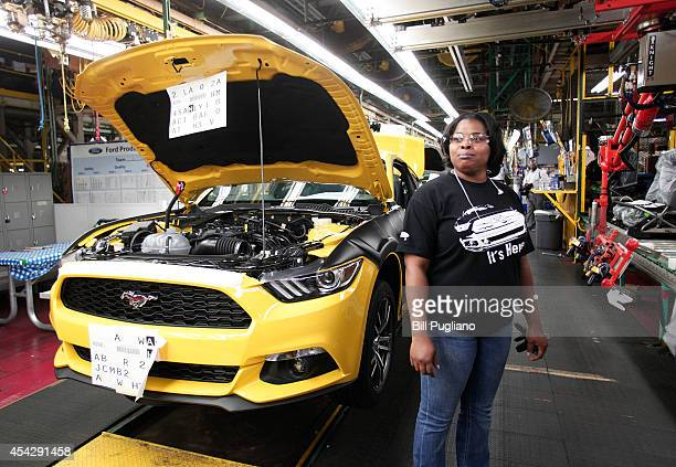 A worker stands near an all new 2015 Ford Mustang while it goes through the assembly line at the Ford Flat Rock Assembly Plant August 28 2014 in Flat...