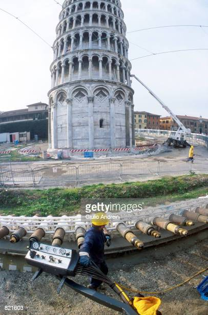 A worker stands near giant drill bits by the Leaning Tower of Pisa March 2001 in Pisa Italy 41 holes or perforations into the earth on the north side...