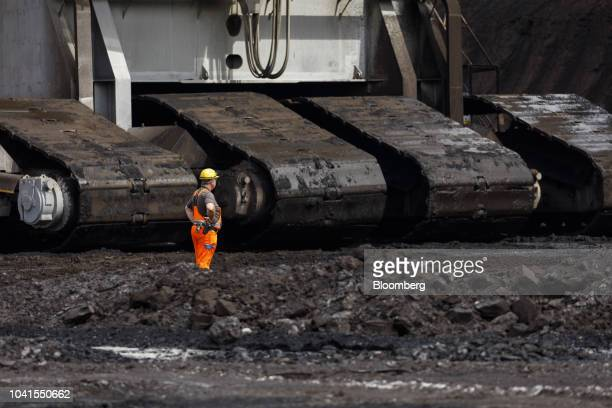 A worker stands near the continuous track wheels of a giant excavator at the open pit lignite mine operated by RWE AG in Hambach Germany on Monday...
