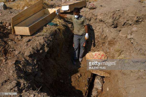 A worker stands next to a corpse which is being moved to the new Hasankeyf cemetery in Hasankeyf at on the banks of the Tigris in southeastern Turkey...