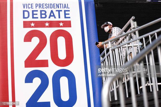 "Worker stands next to a sign that reads ""Vice Presidential Debate 2020"" outside of Kingsbury Hall ahead of the Vice Presidential debate at the..."