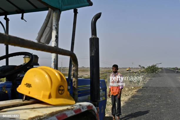 A worker stands next to a vehicle at an under construction sewerage system on the project site for a 920squarekilometer industrial area located on...