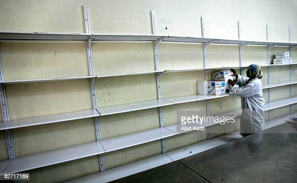 A worker stands next to empty shelves at the Middle East Company for Pharmaceutical Industries September 08 2008 in Bait Hanoun Gaza Strip...