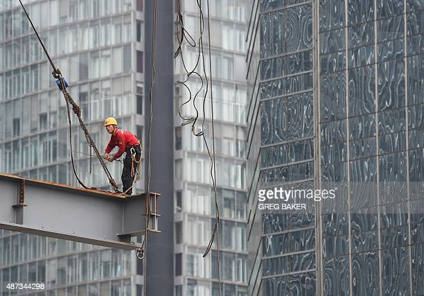 A worker stands on a beam on a construction site in Beijing on September 9 2015 China's government says the world's second largest economy is...