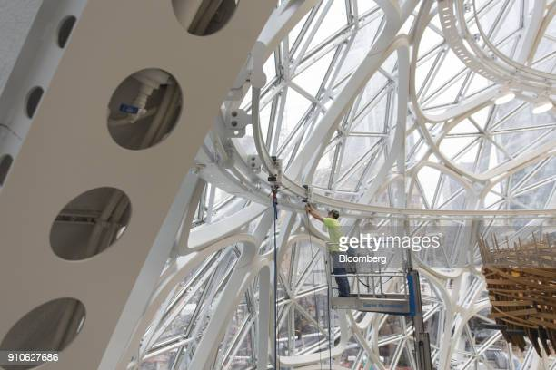A worker stands on a cherry picker while making adjustments inside the Amazoncom Inc Spheres before the opening in Seattle Washington US on Tuesday...