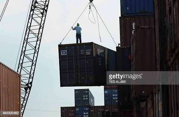 A worker stands on a container at a port in Manila on February 24 2015 Philippine officials voiced confidence the country had escaped a 'boombust...